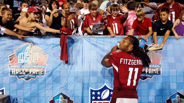 "FILE - In this Aug. 5, 2012, file photo, Arizona Cardinals wide receiver Larry Fitzgerald (11) signs autographs on the sidelines during the fourth quarter of the Hall of Fame exhibition football game against the New Orleans Saints, in Canton, Ohio. The NFL's ""Character Playbook"" initiative has reached 88,000 students nationwide in its first year, and will expand to 360 more schools and introduce a new virtual classroom experience called ""Character Playbook LIVE."" Cardinals' Larry Fitzgerald says ""What makes this program so valuable is that it lays the foundation early and provides kids the skills and understanding to develop these qualities that not only benefit them individually, but also the communities they live in."" (AP Photo/Scott Galvin, File)"