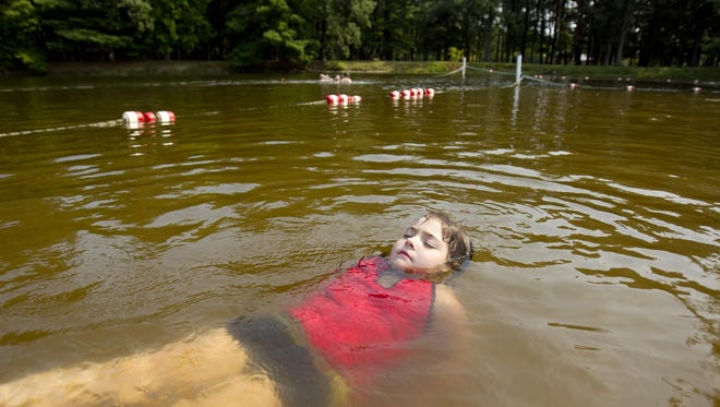 Bella Williams, 6, floats on her back in the swimming area of Lake Kaunewinne at North Wood County Park north of Pittsville on Aug. 21, 2013.