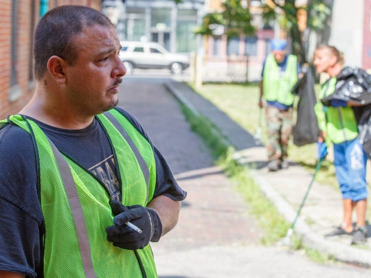 "Domminick ""Joe"" Horsley works for the Jobs Van program on Wednesday, July 11, 2018, in Over-the-Rhine. The new program pays panhandlers $9 an hour to pick up trash."