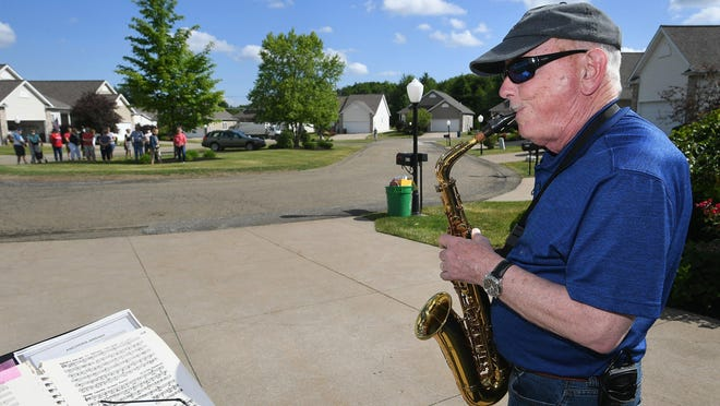 David Hetrick holds a mini-concert on his alto saxophone from his driveway Friday in the Meadows of Summit housing development in Summit Township. Hetrick, 73, has been performing every morning since Memorial Day as a way to entertain his neighbors during the COVID-19 lockdown.