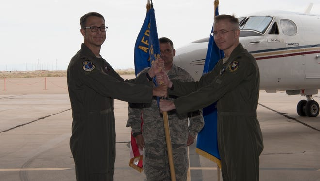 Col. Scott Cain, Arnold Engineering Development Complex commander, hands the 704th Test Group guidon to Col. Charles Cain, 704th TG commander during the 704th TG change of command at Holloman Air Force Base, N.M. July 10, 2018. During the ceremony, the responsibility of the 704th TG was entrusted to Col. Charles Cain.