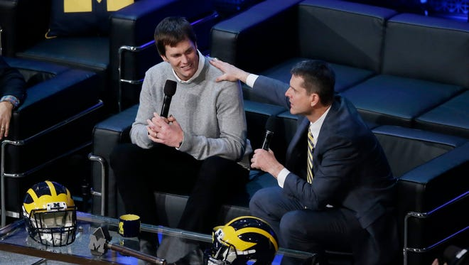 Michigan football coach Jim Harbaugh, right, talks with quarterback Tom Brady during the Signing of the Stars spectacle Feb. 3, 2016 in Ann Arbor.