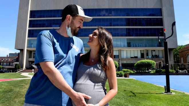 """All smiles, Ben and Gabrielle McCarthy of South Rockwood take a stroll outside at Henry Ford Hospital, Detroit, as she has completed a milestone of 30 weeks into her pregnancy with the twin girls. """"The girls kick all day everyday,"""" said Gabrielle. """"They actually stick out and my stomach is lumpy."""""""