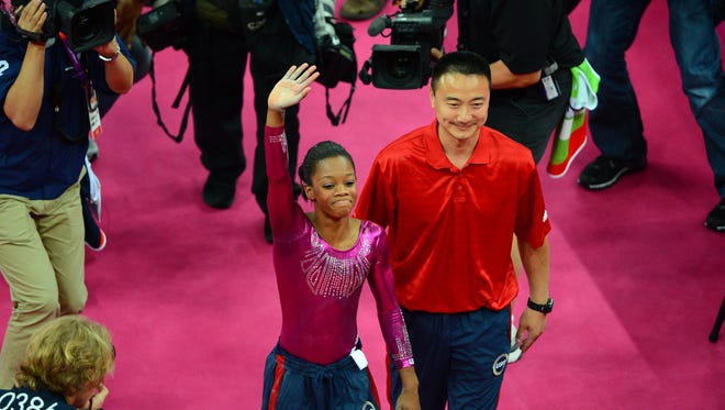 Gabby Douglas celebrates with coach Liang Chow after her performance in the floor exercise in the women's individual all-around final during the London Olympics at North Greenwich Arena on Aug. 2, 2012.
