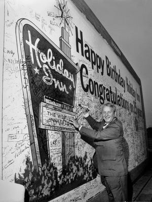 Dave Darnell/The Commercial Appeal files Adding his name to a 12-foot by 25-foot card wishing Holiday Inns a Happy 25th Birthday is founder and chairman of the board Kemmons Wilson on Sept. 8, 1977. More than 8,000 employees and their families' special guests were invited to a party held at Libertyland to celebrate the event.