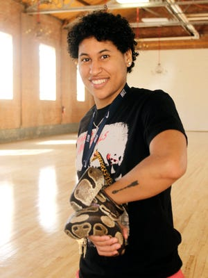 WNMU student Nalani Hernandez holds a snake at the reptile show at Western New Mexico University's Graham Gym on Thursday.The reptile show was sponsored by the WNMU Art Club.