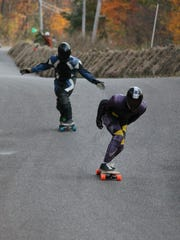 Two skaters fly down Jester Hill Road in Bainbridge during the finals of the 2012 Soldiers of Downhill competition.