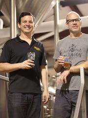 Hexagon Brewing Co. co-owner Matt McMillan, left, and head brewer and majority owner Stephen Apking sample their beers in their Dutch Valley Drive brewery in Fountain City.