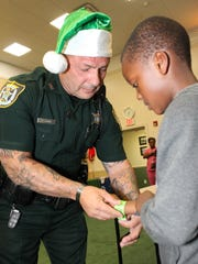 Clifford Labbe puts a wristband on a child participating