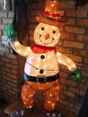 A 'cowboy' Frosty the Snowman lit up for the holidays.