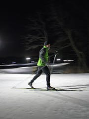 A cross-country skier makes his way around the lighted