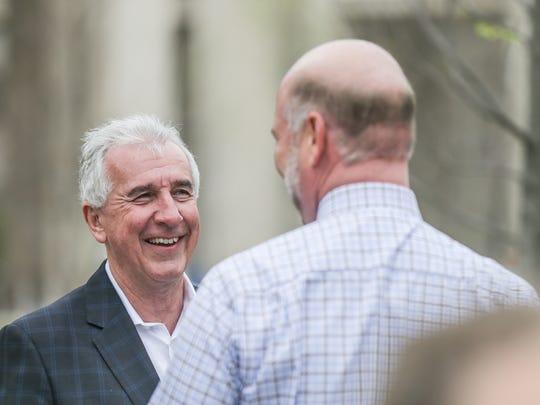 Jay Ricker, chairman of Ricker Oil Co., left chats