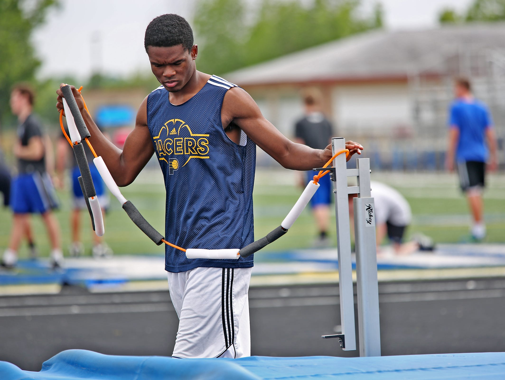 Hamilton Southeaster athlete Francis Ehigbai puts up a practice bar for high jump practice, June 1, 2015.