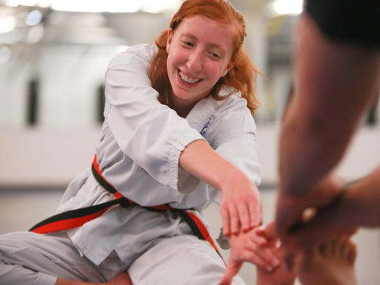 Hannah Jarrett of Canton demonstrates some stretching she does to the Detroit Free Press with the help of Master Dan Vigil on Tuesday September 1, 2015 at Dan Vigil's Academy of Taekwondo in Northville. Vigil believes he's found a therapy for kids with ADD/ADHD like Hannah using Taekwondo to alleviate the symptoms.