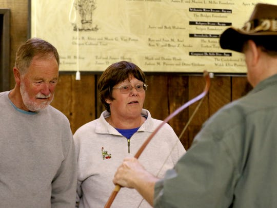 Dr. Leland Gilsen, right, shows a replica of a Native American bow to  Bob Van Denheuvel and Susan Schooler, of Olympia, Wash., at the Traveling Museum of Oregon Prehistory at Champoeg State Park in St. Paul, Ore., on Saturday, Oct. 17, 2015.
