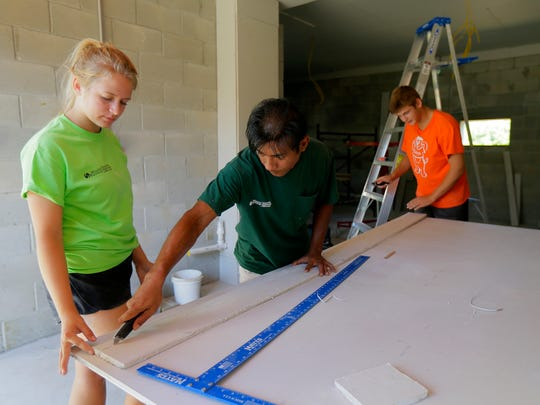 (center) Harry Pangemanan, an undocumented immigrant from Indonesia who is helping rebuild Sandy homes on the Shore, works on a home with volunteers from Community Christian Reformed Church in Kitchener, Ontario, including Nicole Nusselder, 17, and Matthew Perry, 15, on Cedar Avenue in the Leonardo section of Middletown, NJ Friday August 19, 2016.