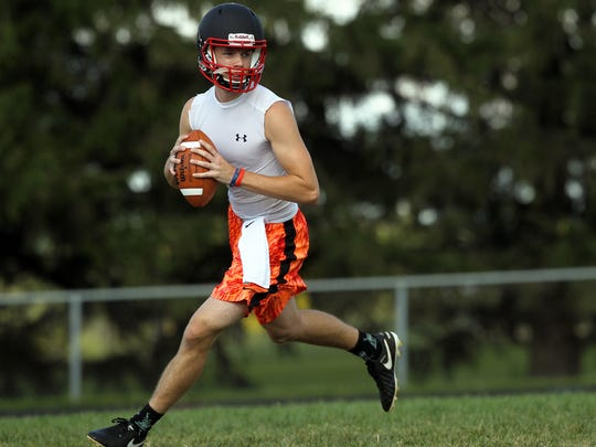 West Branch quarterback Beau Cornwell runs drills with teammates during practice on Monday, Aug. 7, 2017.