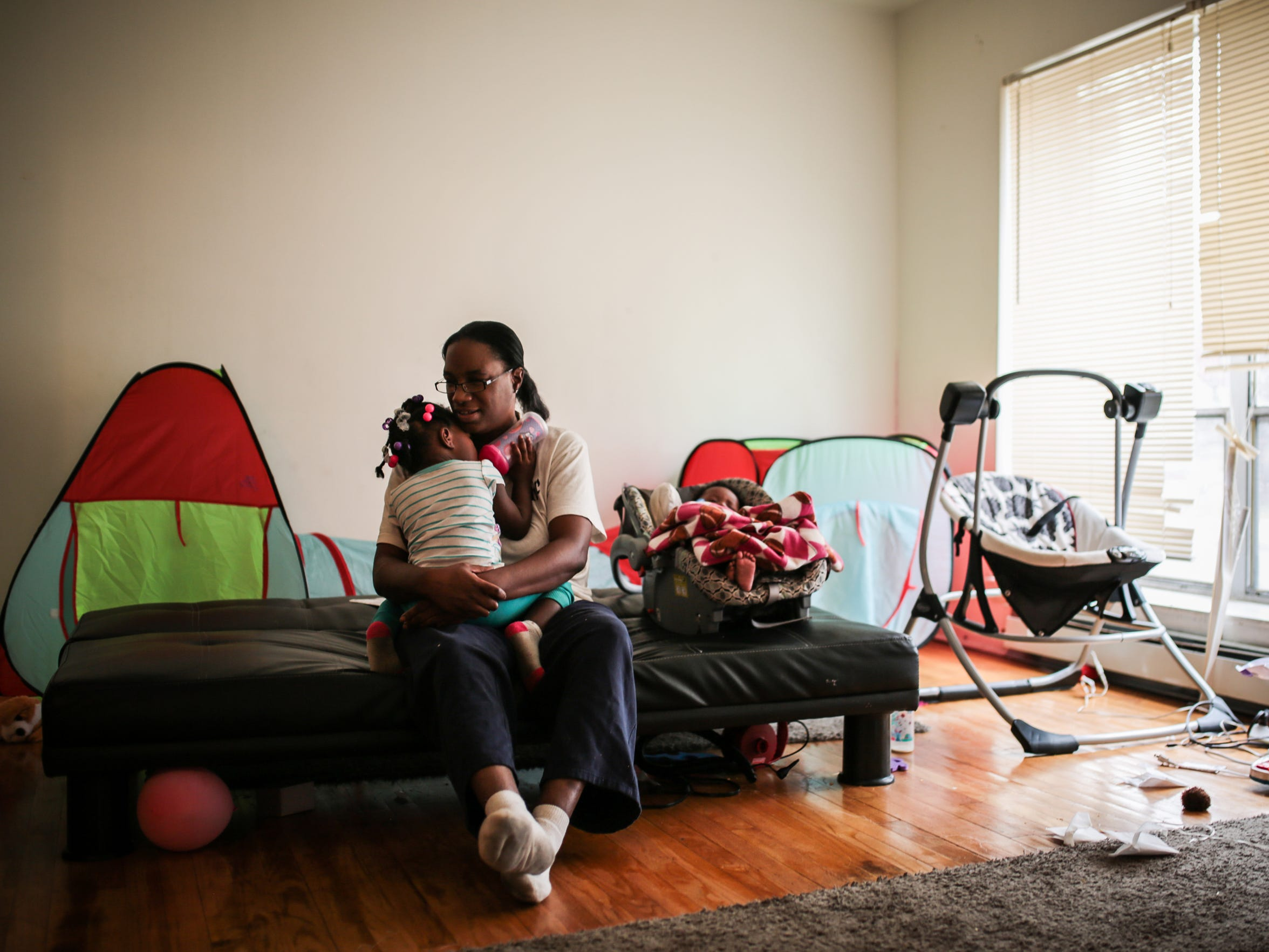 Felicia Darnell, 40, of Detroit, holds her 2-year-old daughter Zoey Darnell, 2, while her 4-month-old daughter Geneva Darnell sleeps inside their apartment on Detroit's east side.