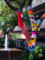A tree swaddled in yarn in the pocket park near the