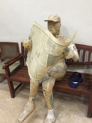 A statue made of newspaper greets visitors to the lobby
