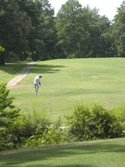 A golfer hits a tee shot at Timber Trails.