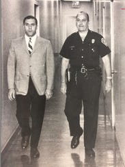 Police Officer Ralph Boryszewski with one of his attorneys, John Parrinello, attends his public hearing on disciplinary charges that he discredited the Rochester Police Bureau in 1968.