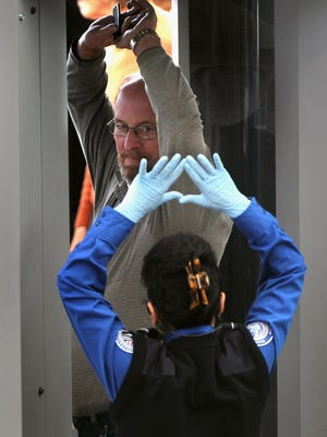 The Transportation Security Administration conducts a full-body scan of a traveler at Denver International Airport on Nov. 22, 2010. Civil-rights groups are asking a federal court to force TSA to adopt formal regulations governing the scanners.