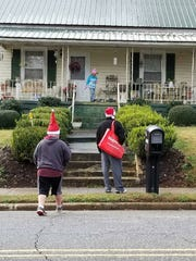 Kevin Norris, at right, goes up to someone's house to deliver a Christmas card. The 42-year-old Anderson resident delivered hundreds of Christmas cards to people in need in Anderson this year.