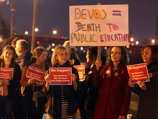 People gather for a protest against Betsy DeVos outside