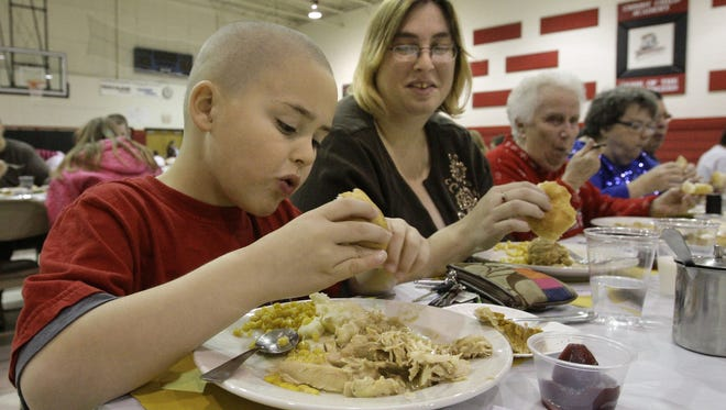 Odin Rowe, 6, enjoys a turkey dinner with his mother, Amanda, at Immaculate Conception Church.