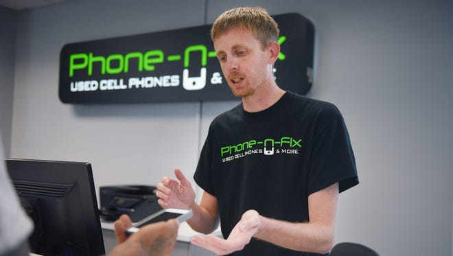 Justin Kirkvold, Phone-N-Fix store manager, puts a phone case on an iPhone for a customer Friday, July 28, at the 3800 West 41st street location in Sioux Falls.