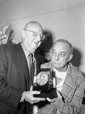 """Buster Keaton, right, the dead-pan comic of silent films, receives an award honoring him for his contribution to early-day movie entertainment on Dec. 14, 1955. Jesse Lasky, a pioneer Hollywood film producer, presented the award, known as a """"George,"""" because it was sponsored by the George Eastman House of Rochester."""