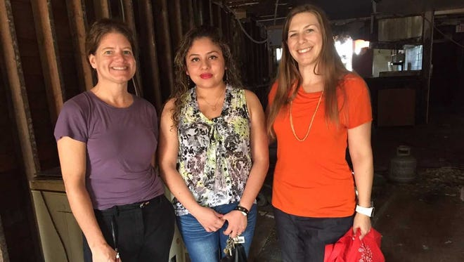 Leticia Munoz Hernandez (center) plans to open a new restaurant in a long-vacant, dilapidated building in Milwaukee's Silver City neighborhood. She is flanked by Shannon Boone (left) and Celia Benton, of Layton Boulevard West Neighbors Inc., a nonprofit neighborhood group that is leading the redevelopment project.