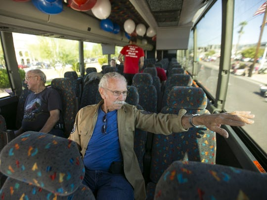 Eighty-seven-year-old Joe Kauffman, a Korean War veteran and former Tour West America charter bus driver, rides in a Tour West America charter bus, greeting parade-goers in Phoenix, on Nov. 11, 2016.
