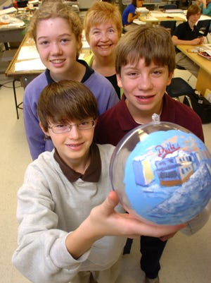 Southern Delaware School of Arts students show off a ball painted with a scene of Rehoboth Beach boardwalk in this 2010 file photo.
