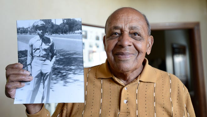 Harold H. Brown, 91, World War II veteran and Tuskegee Airman, holds a picture of himself at 20 years old after he returned home from the war.