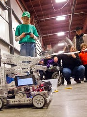 """Audrey Chairvolotti, 11, of Grand Isle, steers a robot through tricky maneuvers Wednesday at the Vermont Show in Essex Junction. Chairvolotti and her siblings built the 'bot as part of the Champlain Shamrocks 4-H Club's """"Aluminum Avian Antics"""" project."""