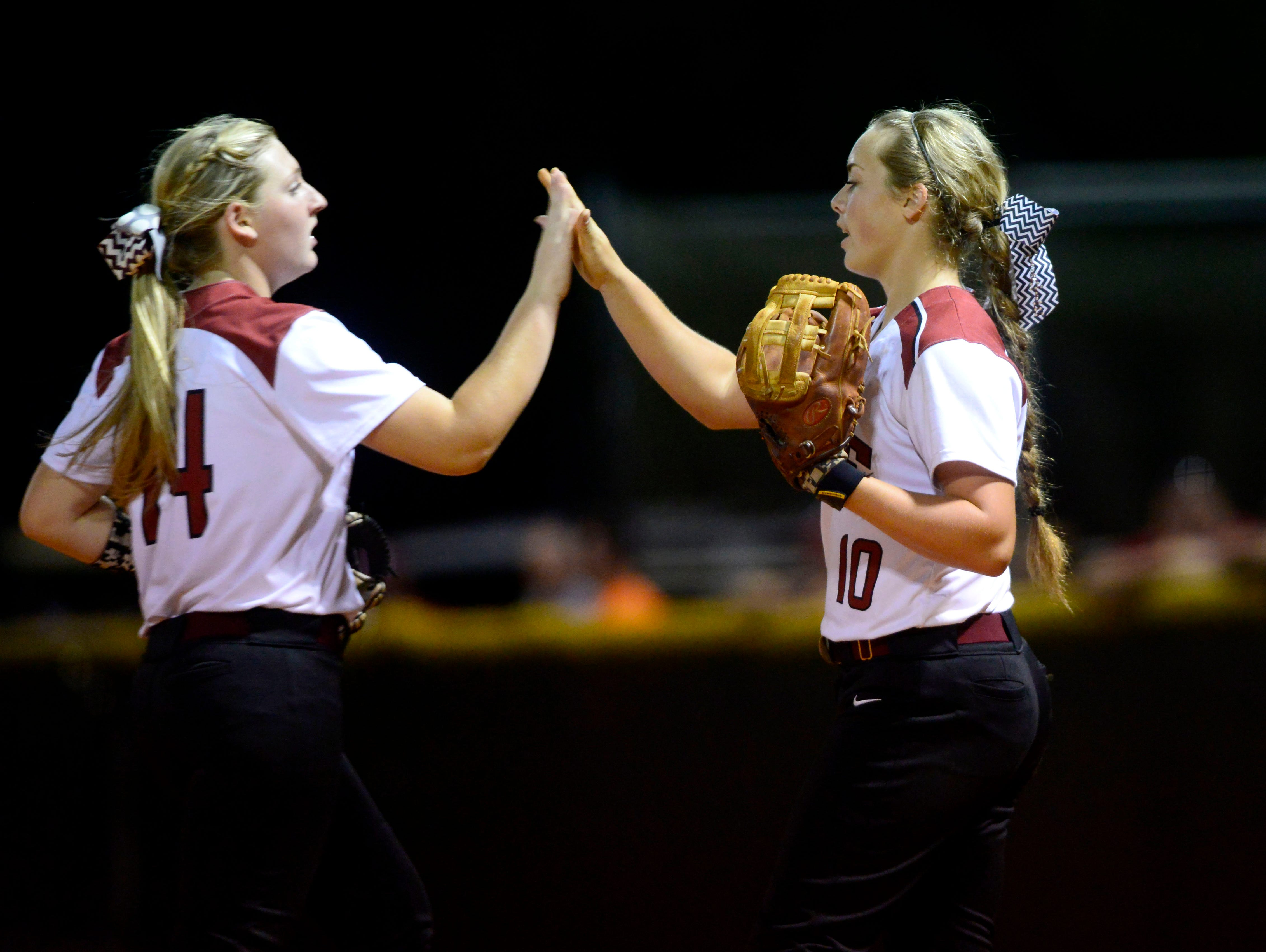 Tate High School pitcher Tori Perkins, right, slaps hands with teammate Samantha Burks after an inning Wednesday in a Region 1-7A quarterfinal game against Lincoln High School.