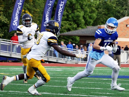 Catholic Central's Nate Anderson (right) tries to elude
