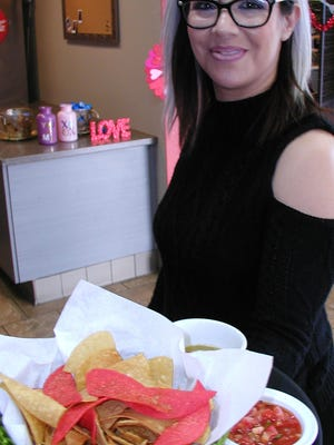 Restaurant owner Adriana Ortega carries salsa and chips to hungry diners.