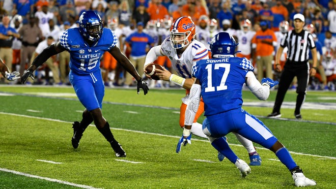 Florida quarterback Kyle Trask (11) tries to avoid Kentucky linebackers Jordan Wright (15) and DeAndre Square (17) during the fourth quarter of last year's game in Lexington, Ky. Trask led the Gators to a 29-21 win.