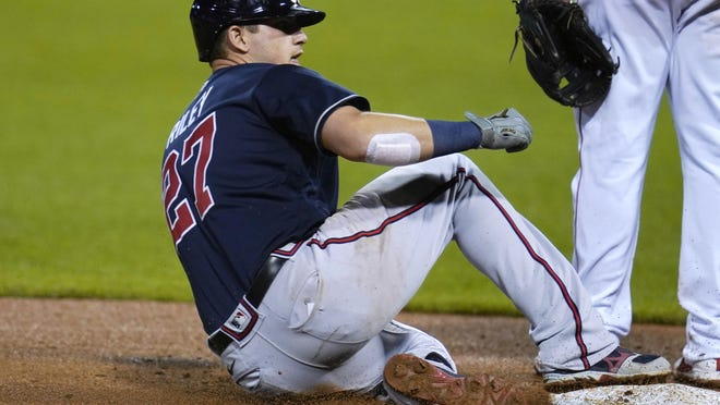 Austin Riley slides safely into third base after his three-run triple Monday.