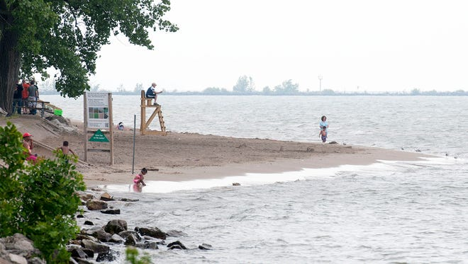 Families spend a warm, summer afternoon at the public beach at East Harbor State Park in Danbury Township on Thursday. East Harbor has been named one of the top beaches in the area.