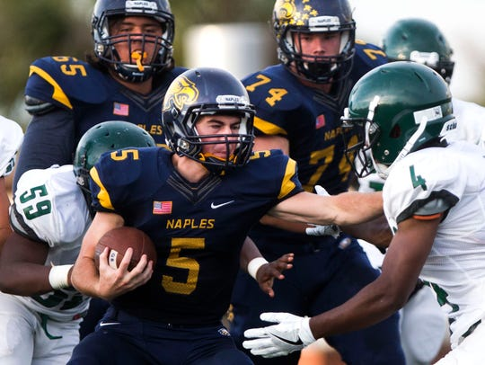 Naples High quarterback Drew Wiltsie runs through defenders during the game against St. Petersburg High School in May.