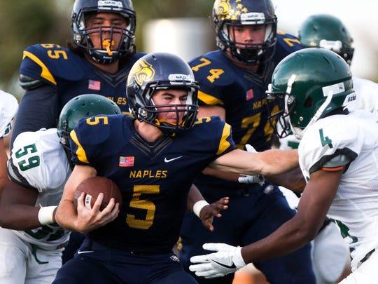 Naples High quarterback Drew Wiltsie runs through defenders during the game against St. Petersburg High School in May.