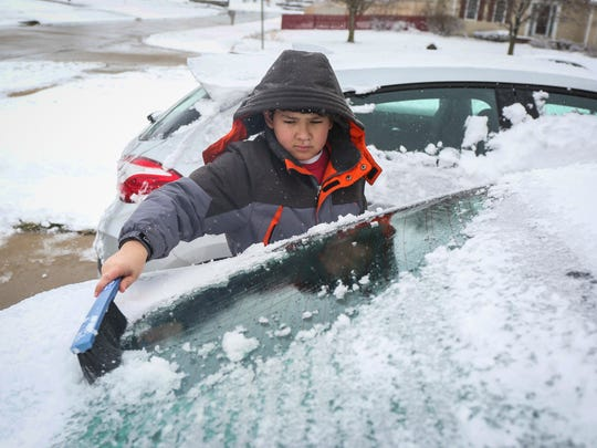 Gavin Firch, 11, cleans snow off his grandma's car