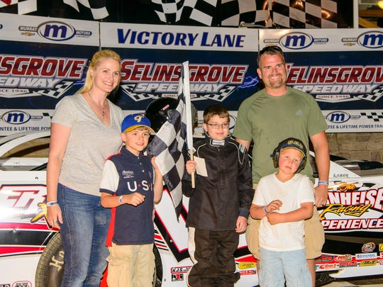 William Dieffenbach, with his family by his side, takes the checkered flag after his ride around Selinsgrove Speedway.