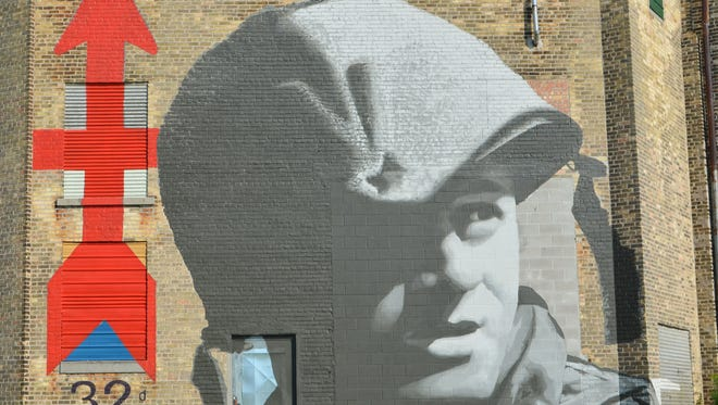Julia Poe/USA TODAY NETWORK-Wisconsin The mural, on the side of the Historic Richter Vinegar Plant, was inspired by a black-and-white photo of a 32nd Infantry Division (Red Arrow Brigade) soldier, D.F. Hirsch of Milwaukee, a Specialist Fourth Class. His image was taken by a military photographer during training at Fort Lewis in Washington state in May 1962, preparing for a potential threat in Berlin. The mural, on the side of the Historic Richter Vinegar Plant, was inspired by a black-and-white photo of a 32nd Infantry Division (Red Arrow Brigade) soldier, D.F. Hirsch of Milwaukee, a Specialist Fourth Class. His image was taken by a military photographer during training at Fort Lewis in Washington state in May 1962, preparing for a potential threat in Berlin.