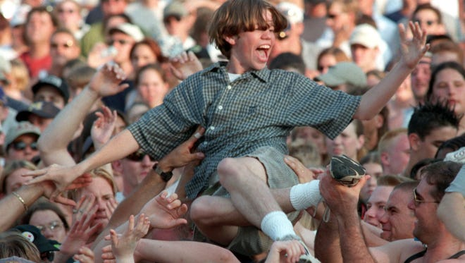 An unidentified crowdsurfer rocks out to Cowboy Mouth as the sun begins to set during the band's performance at springfest on Sunday, May 17, 1998.