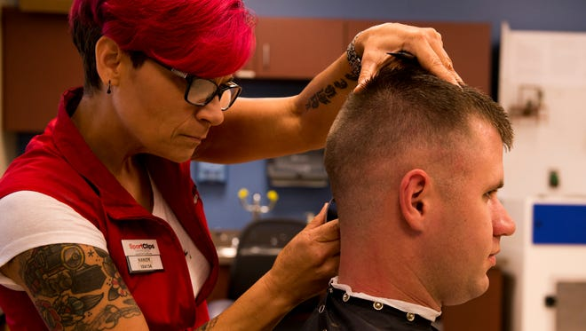 Chris Reed, an active duty Military Police officer who is volunteering at the Veteran's Festival, gets his haircut by Kandy Bradley. Free haircuts are one of the many services the festival offers toward veterans and their families.
